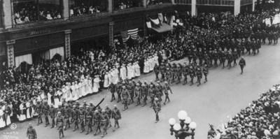 American troops march in a parade down a city street with many onlookers on the sidewalks.