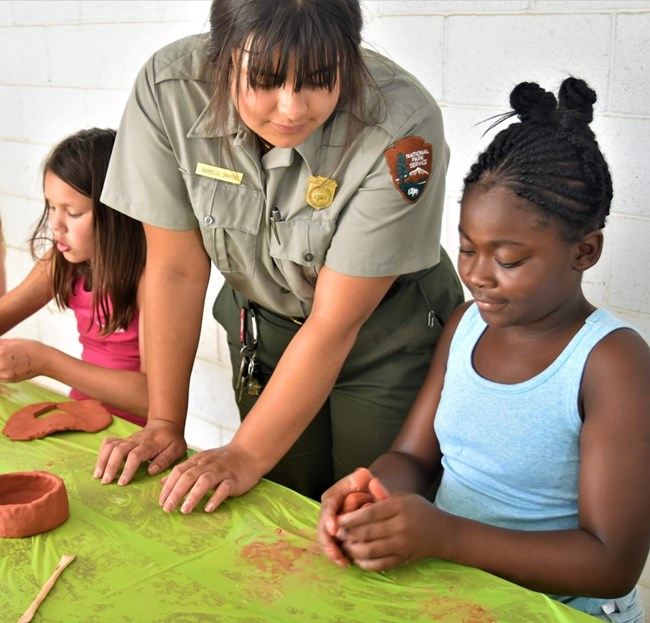 Ranger and Girl Scout making pottery