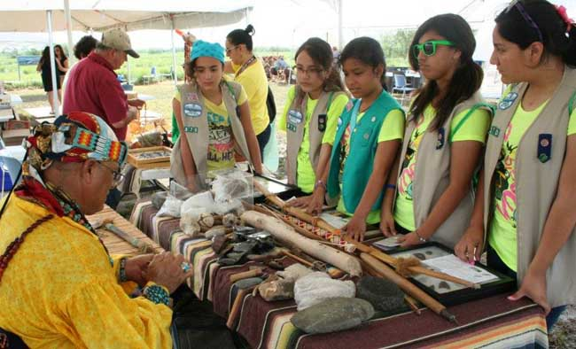 Girl scouts observe demonstration and examine artifacts.