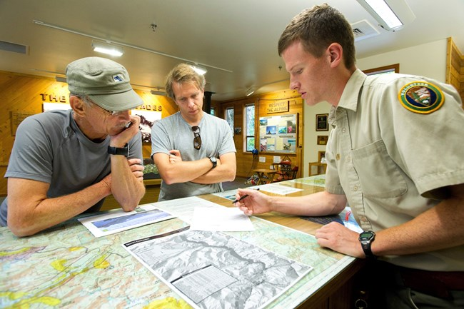 Park visitors Aaron and Richard Hoff seek advice at the Wilderness Information Center. August 28, 2012, Marblemount, Washington, Campers get an update on backcountry conditions from a park volunteer at NPS by Davi