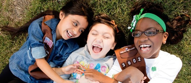 Girl Scouts smiling laying in the grass.