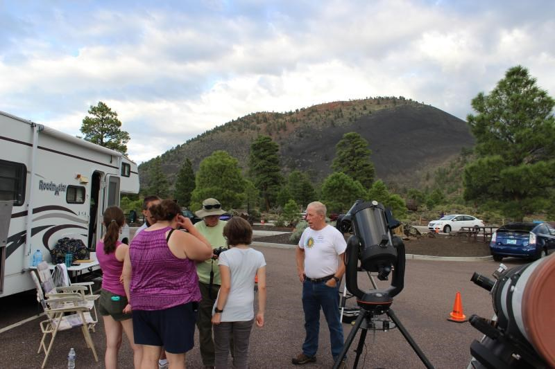 Volunteer astronomers speaking with visitors near telescopes, with Sunset Crater Volcano in the background.