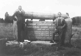 2 men standing with wooden entrance sign to CCC camp