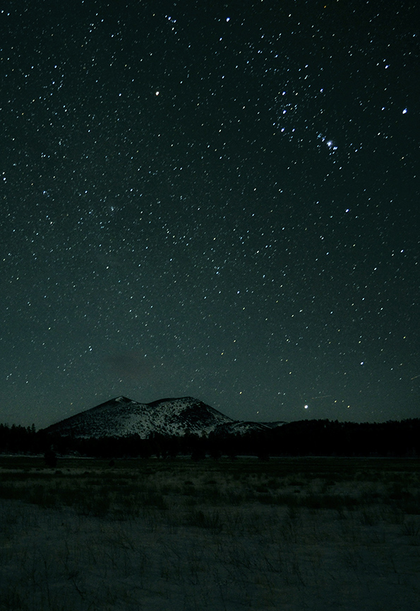 a volcanic cinder cone under a dark night sky with many stars