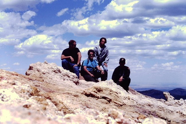 Four people sit on yellow-white rocks high above surrounding desert and forest terrain. One of them is a park ranger. They group is on top of Sunset Crater Volcano. White clouds dot the blue sky above them.