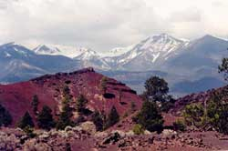 Cinder and lava formations, with snow-covered peaks in background