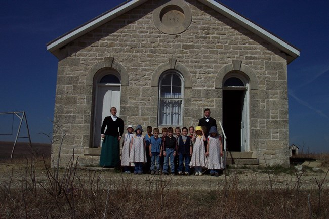 photo of one room schoolhouse with children dressed out in historic clothing