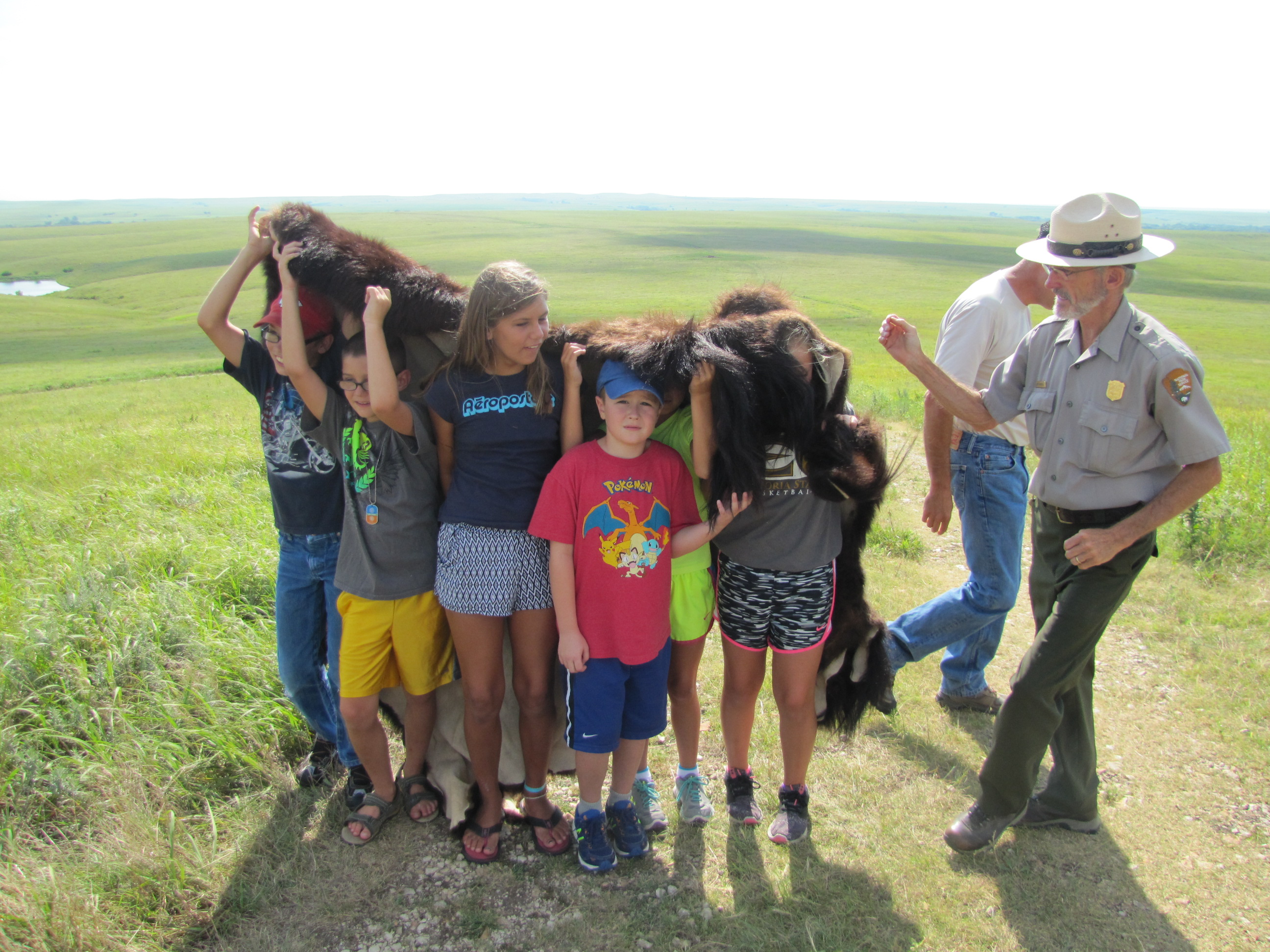 Kids wear a bison robe to simulate bison in the prairie