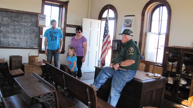 volunteer providing information to visitors at the one room schoolhouse