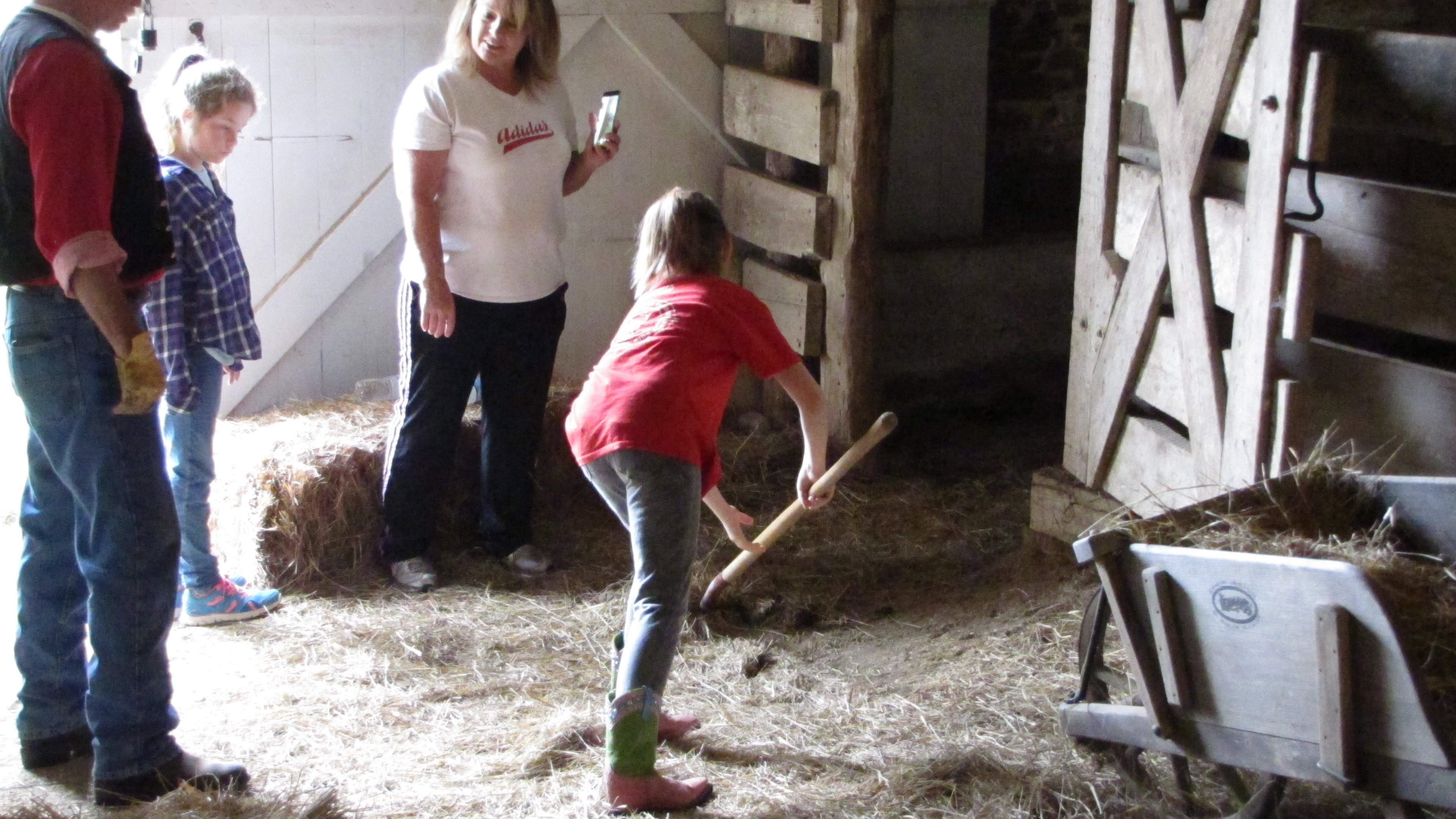Kids doing chores in the barn using a pitch fork