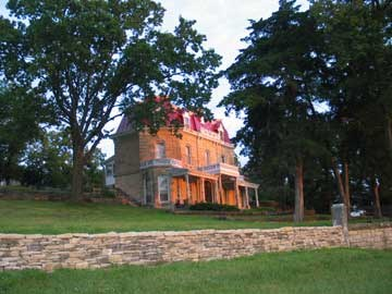 Image of the three story limestone mansion with the rays of sunrise hitting the front side