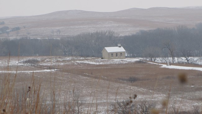 Snow on the prairie with the schoolhouse in the distance