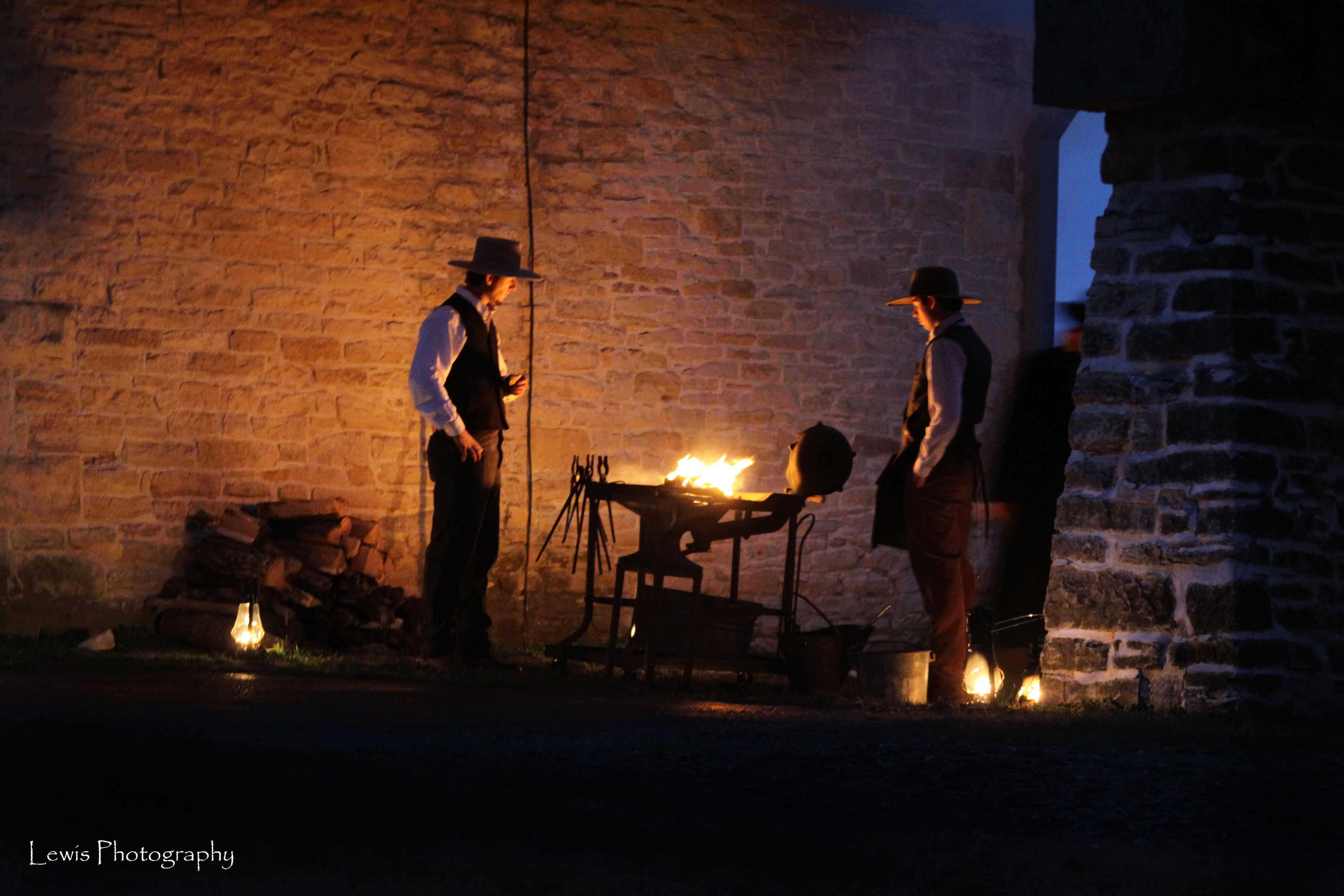 cowboys working hot iron in the dark with lanterns lit