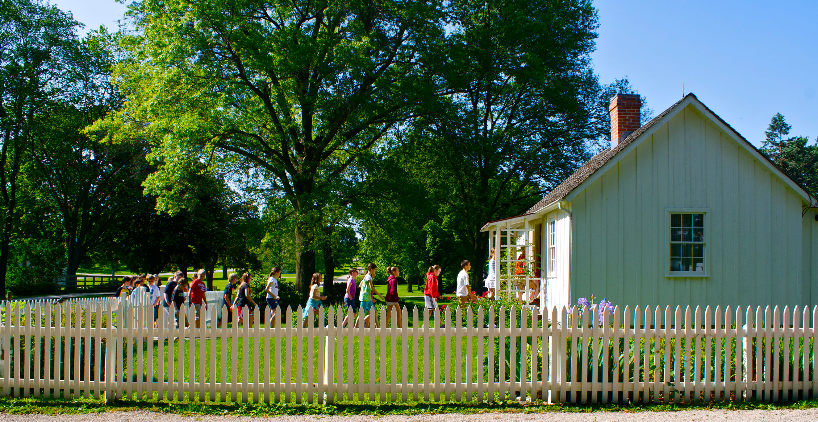 Children line up as they enter a small white cottage at a historical park.