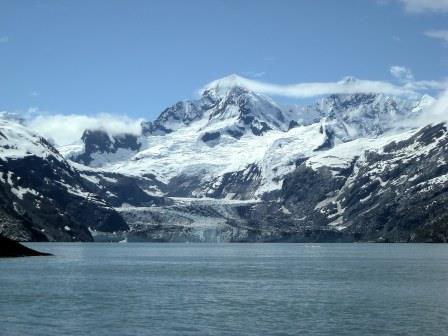 A tidewater glacier with mountain peaks.