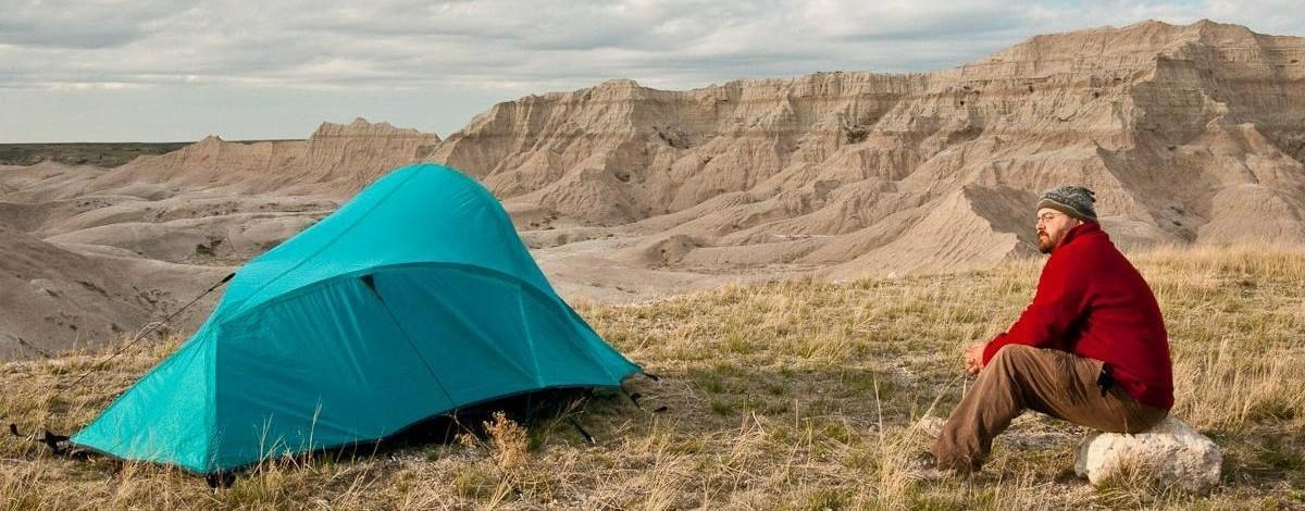 a camper in a red jacket sits next to his blue tent, pitched in grasses with badlands buttes in the background.