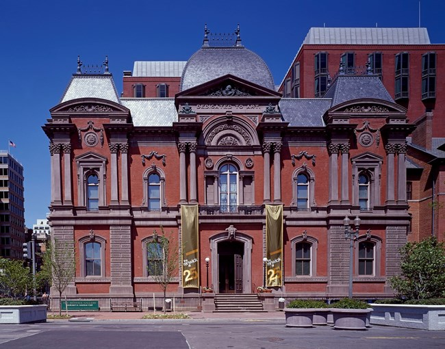 Contemporary photograph of the Renwick Gallery designed in Second Empire style with mansard roof and ornamental massing.