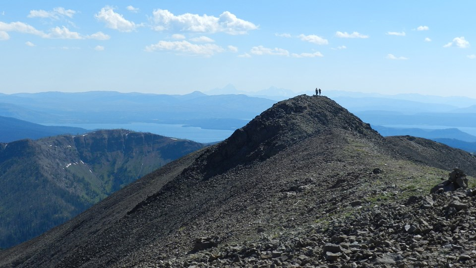 Two hikers standing on the rocky summit of Avalanche Peak