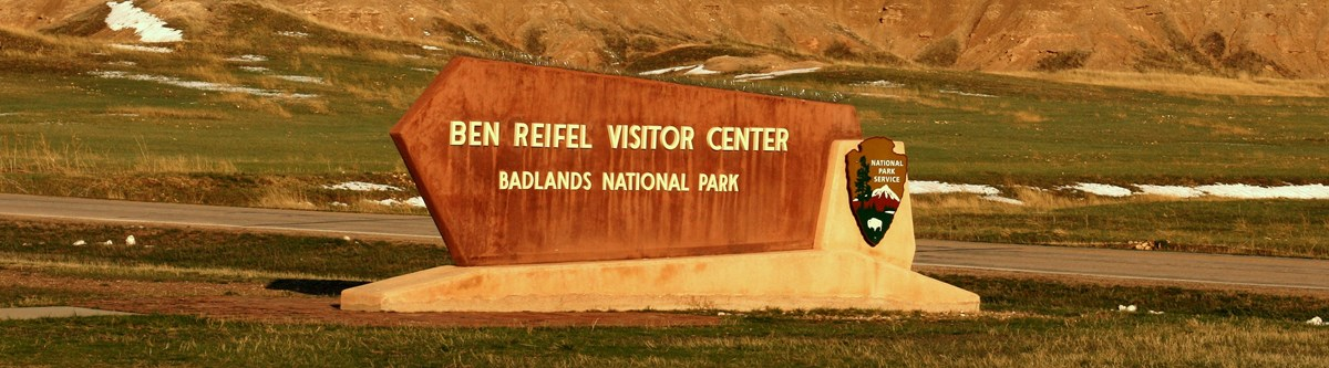 a sign reading ben reifel visitor center sits in front of a road and badlands formations, all bathed in a warm sunset glow.