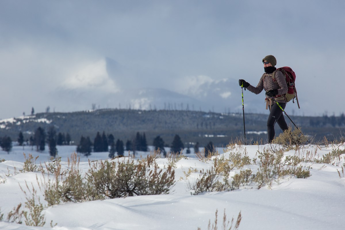 A solitary skier glides along fresh snow on Blacktail Plateau with mountains in the background.