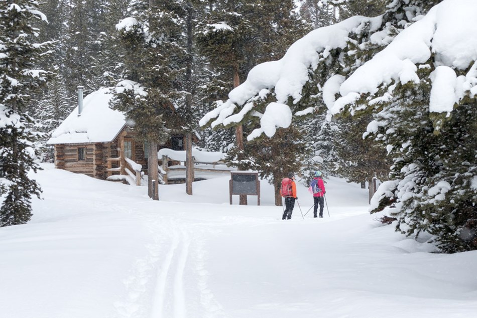 Two skiers wait near the log registration building along the Indian Creek Loop Ski Trail.