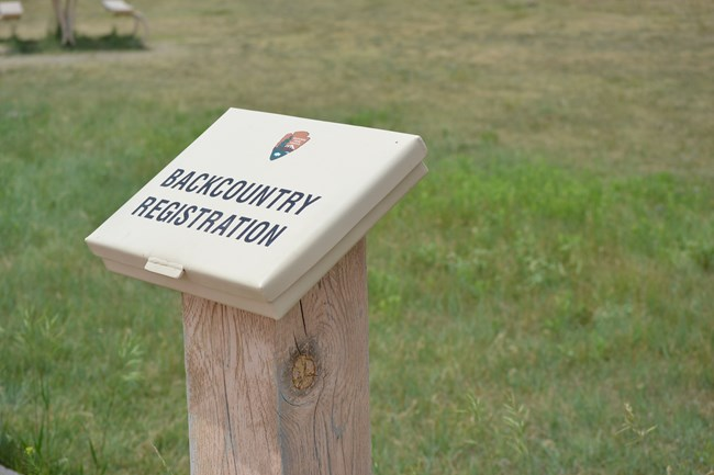 a tan box labeled backcountry registration in front of green grass.