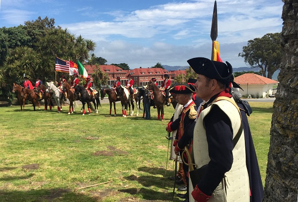 A group of historic reenactors in a field dressed in Spanish Colonial attire with flags and horses.