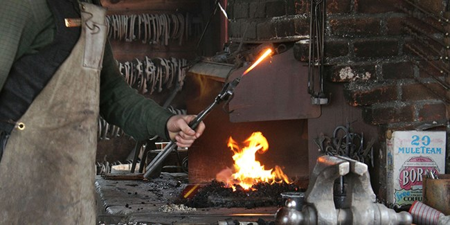 Park Ranger holds hot iron near the forge during a demonstration.