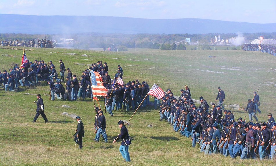 A long line of re-enactors portraying Union soldiers.