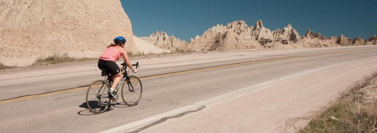 a biker rides up a paved hill with jagged badlands spires in the background