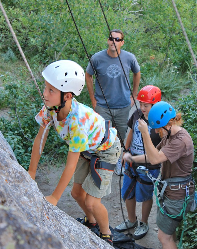 Youth climbing and participating in the climbing experience program