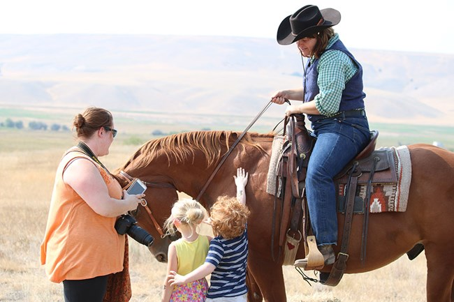Ranger on horseback with mother and children petting the horse.