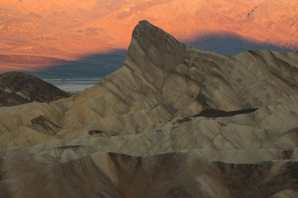 Golden hues illuminate highly eroded badland hills during sunrise.