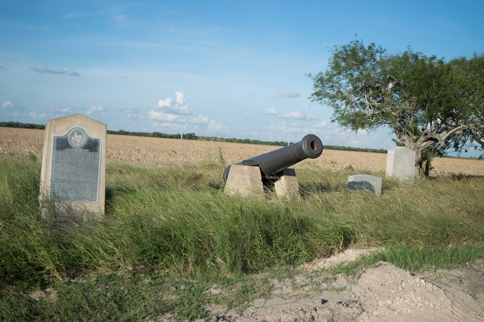 Stone historical marker and replica cannon by the roadside.
