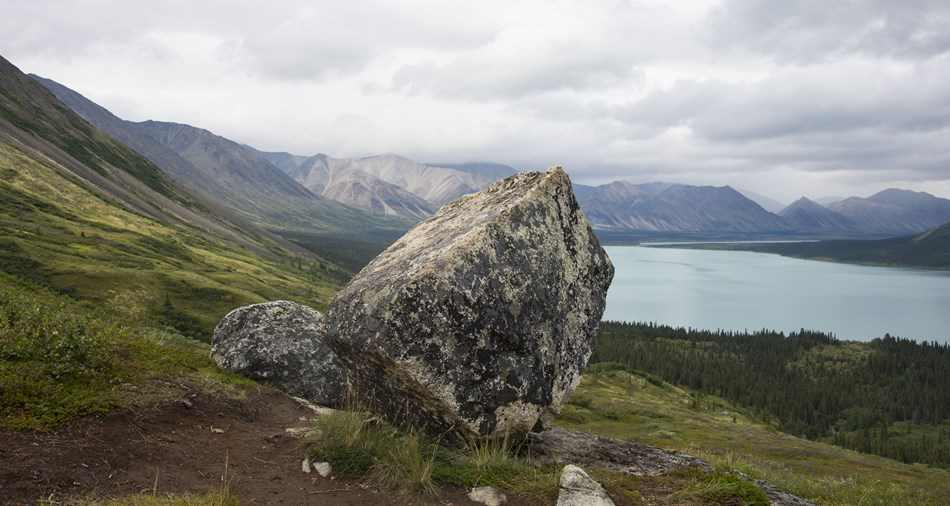 a large boulder balanced on a hillside with mountains and a lake in the background