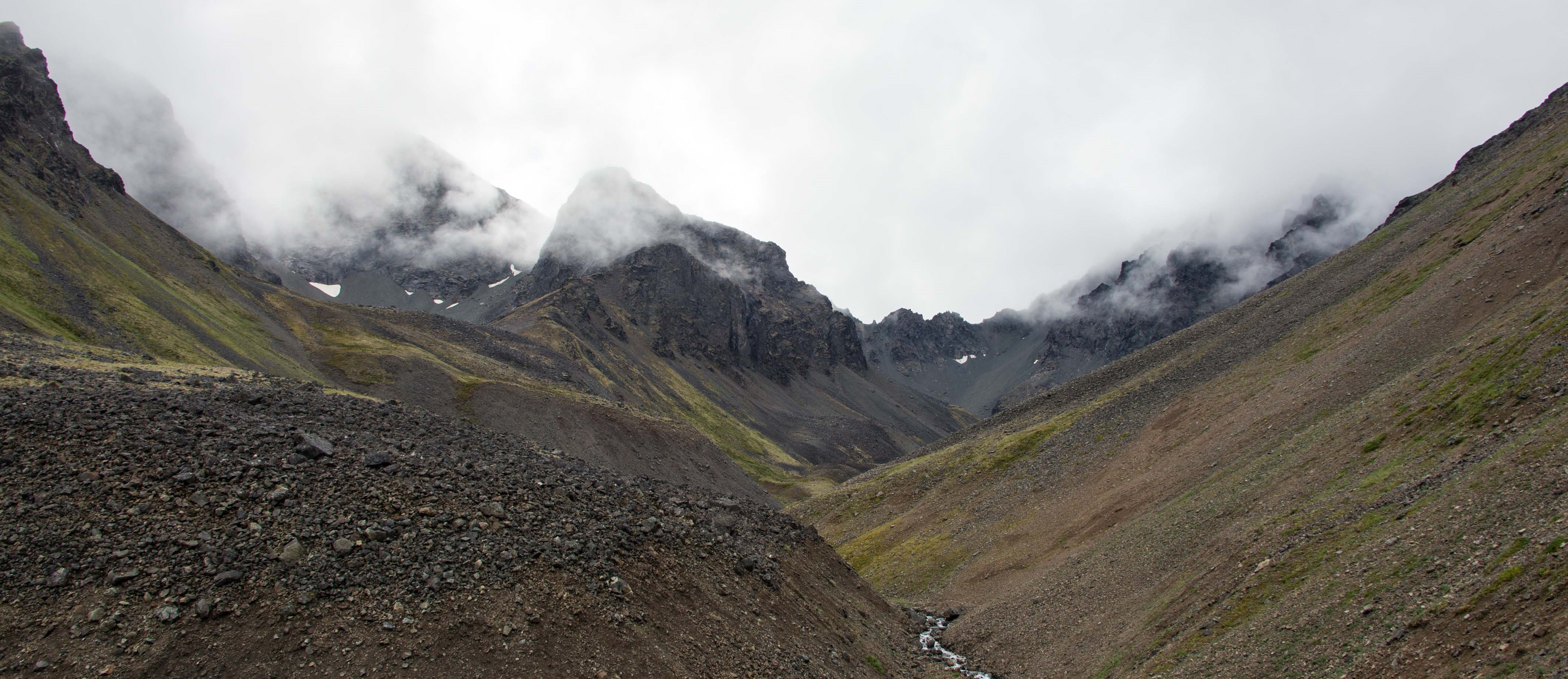 rocky peaks emerge from the clouds in a dramatic valley