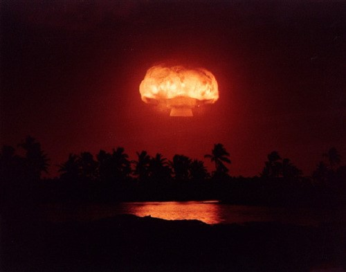 A bright orange mushroom cloud rises over a dark red sky