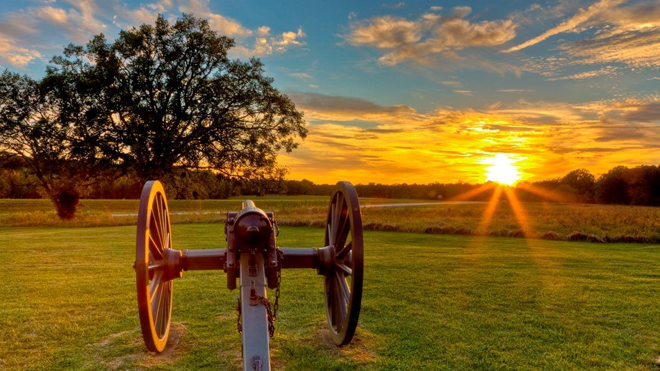 A cannon in a battlefield at sunset.