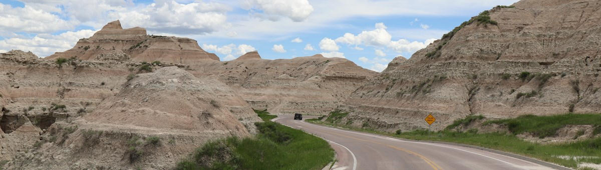 a paved road curves between a low point in a badlands butte, where a black car drives away.