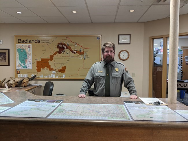 a bearded park ranger smiles from behind a tall desk with a map of the park on the wall behind him.