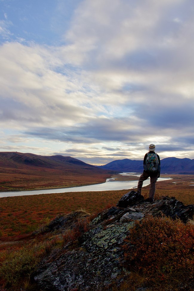 A visitor on the top of a mountain looking out towards the Noatak River