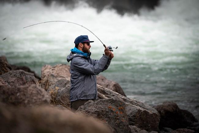 Angler casting line at Jackson Lake Dam