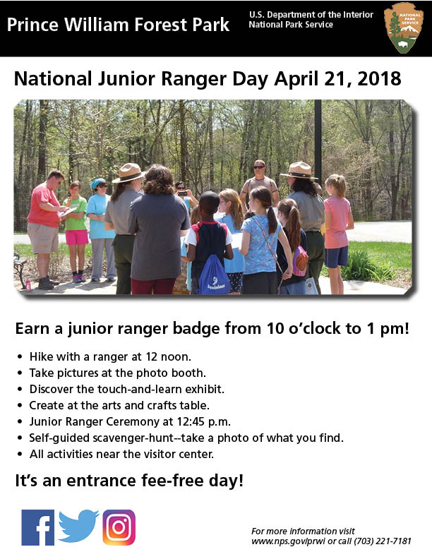 Two park rangers give out the junior ranger badges to a group of children