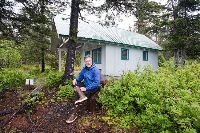 A man sits on a log in the woods, in front of a single room cabin.
