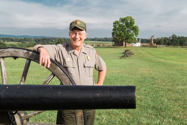 Ranger stands by cannon on the battlefield.