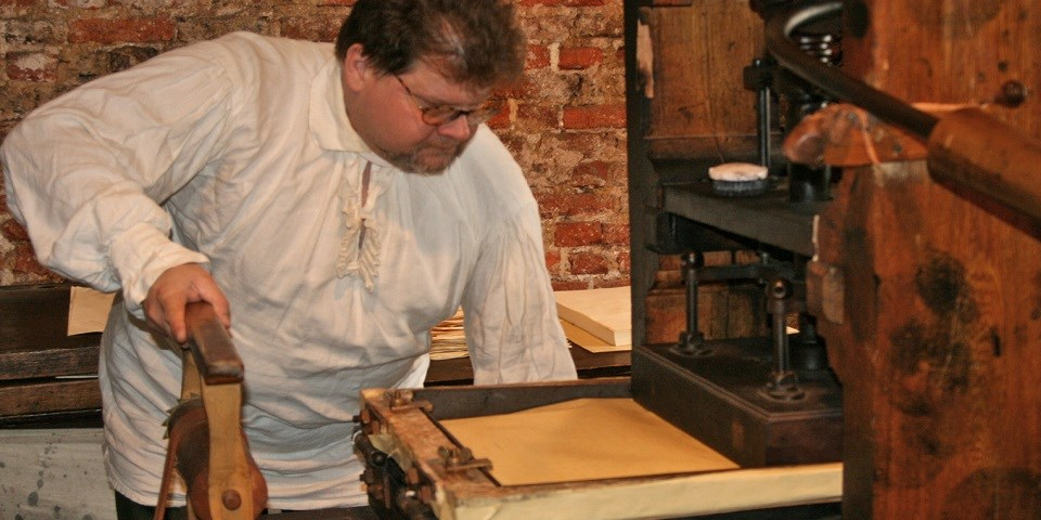 Color photo of man in 18th-century costume demonstrating on a printing press.