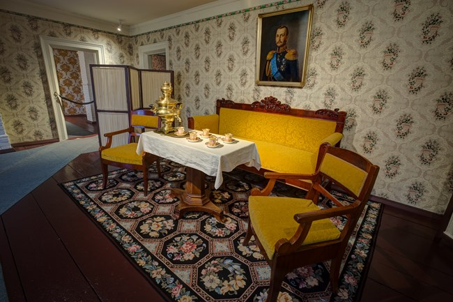 The reception room, which contains a tea setting with furniture, under a portrait on the wall of Czar Alexander.