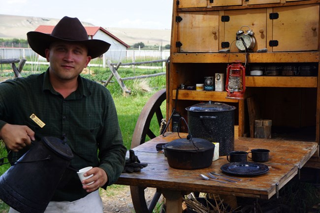 Ranger in historic dress pours coffee during Chuckwagon program