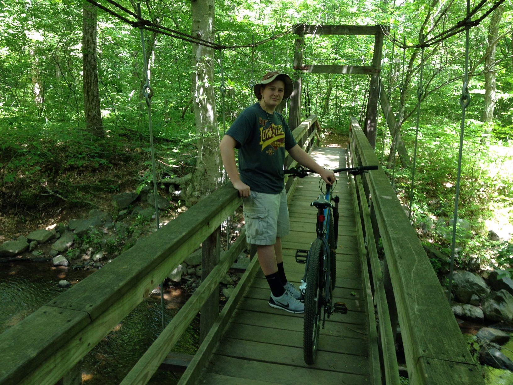 A young man walks his bicycle over a bridge on Laurel Trail in the summer.