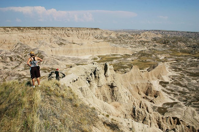 two hikers stand on the high point of a butte, looking down into badlands formations as they stretch toward the horizon